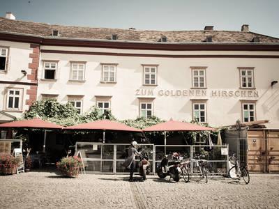 """Außenansicht des Stadtgasthaus """"Zum goldenen Hirschen"""" am Dreifaltigkeitsplatz"""